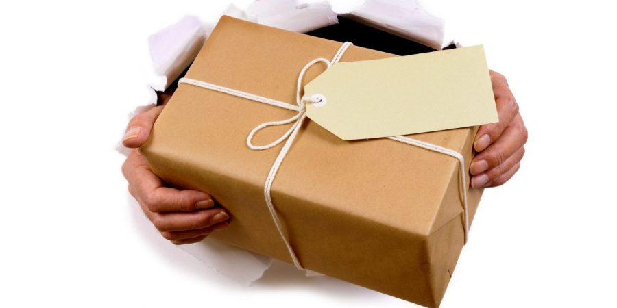 Man hands delivering or giving parcel through torn white paper background