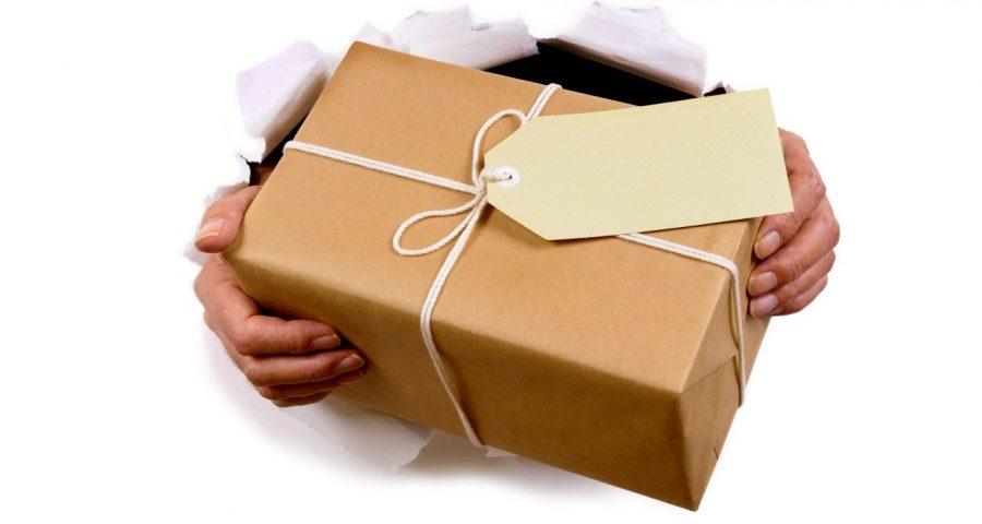 Man hands delivering or giving parcel through torn white paper background